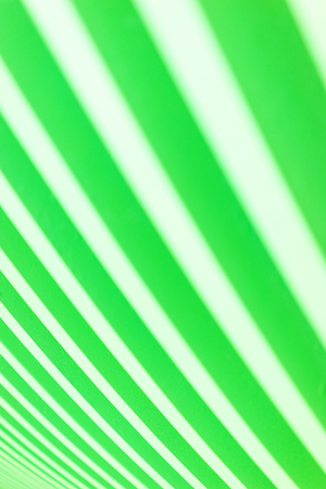 Bright stylish abstract background of wooden boards painted in bright green color. Alternation of green and white bands. Natural background. Soft focus and shallow depth of field.