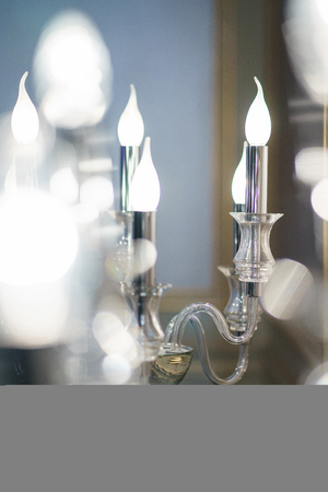 Detail design and interior lighting - white metal wall lamp in the form of candlesticks and candles. Artificial lighting of the room, beautiful lighting. Soft focus and beautiful bokeh. Фото со стока