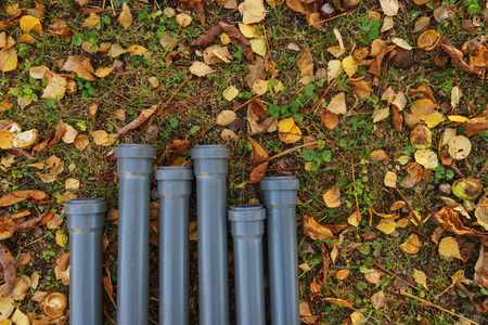 Plastic pipes for water supply and sewage on the ground prepared for installation. Constructions and communications on the site for installation. Plastic pipes on the ground.