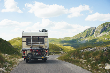 Euro-trip. Old stylish classic motorhome on the road in the mountains. Travel in the summer of Montenegro by car. National Park Durmitor. Banco de Imagens