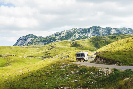 Euro-trip. Old stylish classic motorhome on the road in the mountains. Travel in the summer of Montenegro by car. National Park Durmitor. Stock Photo