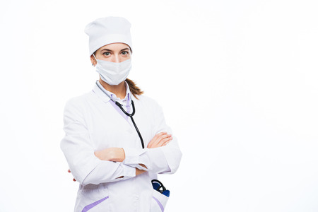 Portrait of an amiable young attractive female doctor, nurse, medical specialist in mask and white uniform. Concept for a medical clinic. Nurse or medical staff on a white background isolated.