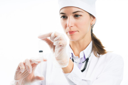 Attractive young woman doctor holds a syringe in hands and prepares an injection for a patient on a white background. Concept of health and medical care. Medic holds the needle and prepares a syringe. Banco de Imagens