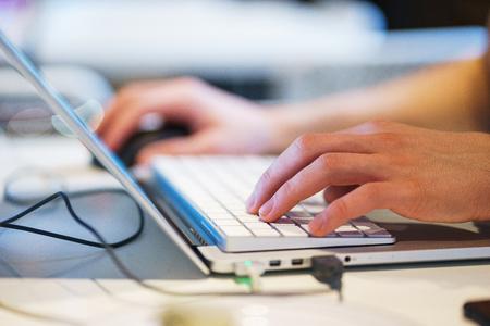 Handen close-up laptop. Computer, handen toetsenbord tijdens het werken met een personal computer. Moderne technologieën en communicatiemiddelen. Mens aan het werk. Routine en creativiteit. Zachte focus en mooie bokeh. Stockfoto