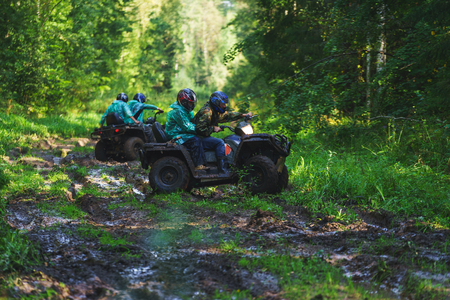 Summer Activities for adults - a trip on quad bikes on the dirty road. Man on ATV unfold on the track in the mud for the continuation of cross-country race. Imagens