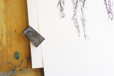 Process of drawing black chalk. Charcoal sketchCanvas and white paper on the artists wooden desktop with an unrecognizable draft. Top view. Stock Photo