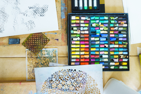 Pastel crayons paint special box. Accessories for painting with pastels. Small pieces of crayons top view. Concept school of art and drawing training. Soft focus. Imagens