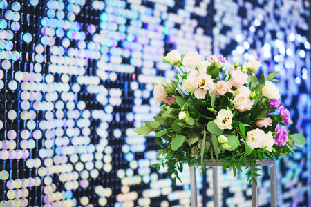 Bright, festive, sparkling, dazzling, abstract background with fresh flowers. Festive decorations and decoration of round shiny metallic sequins. Soft blur and small depth of field.
