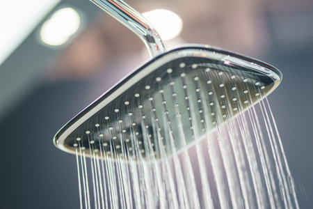 Water pours from the modern shower. Jets of water in the shower close-up. Stylish and luxury plumbing. Water saving and refreshing shower.