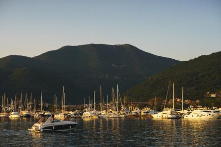 Tapeta wakacje z morzem i jachtami. Luksusowy morski, drogi, wielopokładowy jacht zacumowany na molo. Zobacz miasto i marine z jachtami z morza podczas zachodu słońca. Podróż do Czarnogóry, Tivat Porto Montenegro. Zdjęcie Seryjne