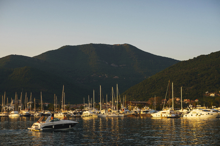 Vacation wallpaper with sea and yachts. Luxury sea expensive multi-deck yacht moored on the pier. View city and marine with yachts from sea during sunset. Travel to Montenegro, Tivat Porto Montenegro. Banco de Imagens