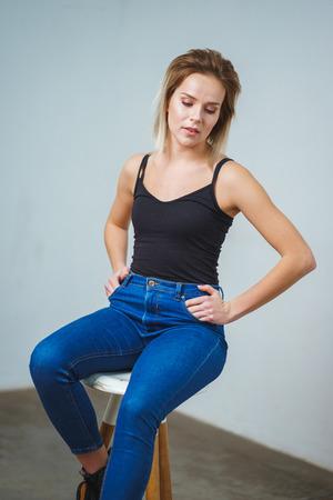 Ensayos de modelos. Modelo de sesión de fotos en estudio. Retratos simples y atractivos para una hermosa joven en una habitación vacía. Snaps. Chica atractiva en jeans, camisa negra. Chica alegre Foto de archivo