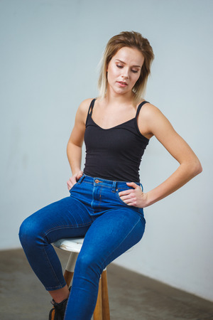 Model tests. Photo session model in studio. Simple attractive portraits for a young beautiful girl in an empty room. Snaps. Attractive girl in jeans, black shirt. Cheerful girl Banco de Imagens