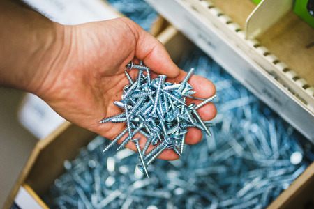 Man holds in his hands many silver small screws for repair and fasteners in a box close-up.