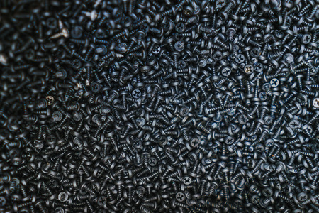Many black small screws for repair and fasteners in a box close-up. Fastener shop and sale of necessary for finishing and repair work in the house. Carpenter's workshop.