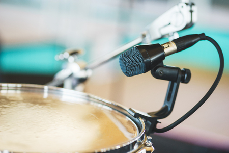 Details of the drum set on the scene close-up. Musical instruments and musical performance. Drums.  Hi-Hat, tam-tam, Microphone close up. Stock Photo