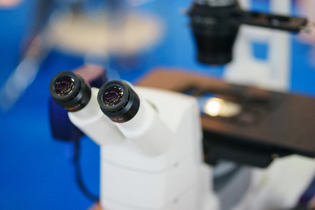 Modern medical instrument microscope for the study of biological samples. Electronic optical device on the desk of a researcher in a scientific laboratory.