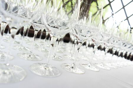 Several rows clear transparent clean glasses for wine champagne on counter prepared for drinks. Catering guest service at event. Luxury nightlife, holidays festival. Soft focus beautiful bokeh.