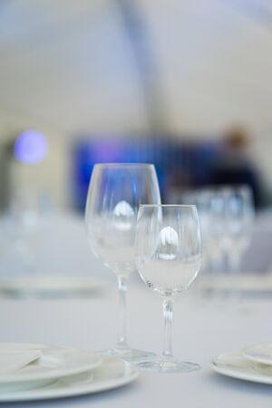 Clean empty glasses and plates on the table in the restaurant prepared for guests. Serving. White dishes and glasses for drinks. Soft focus and beautiful bokeh. Stockfoto