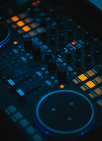Music equipment controller for DJ. Bright neon lamps and glowing buttons on the sound control in a nightclub. Night life. Performance of the musician on a DJ player. Stockfoto