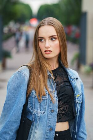 Portrait  young girl denim jacket on the street. Walk through the city streets. Beautiful model in fashionable clothes city park. Girl with a smile looks into camera. Soft focus and beautiful bokeh. Stockfoto