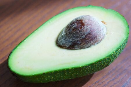 Half fresh avocado, ingredients for cooking on a wooden table in the rays of sun. Vegetarian cuisine, vitamins and fresh vegetables for nutrition. Soft focus. Zdjęcie Seryjne