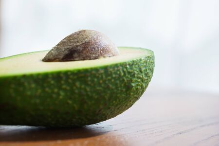 Half fresh avocado, ingredients for cooking on a wooden table in the rays of sun. Vegetarian cuisine, vitamins and fresh vegetables for nutrition. Soft focus.