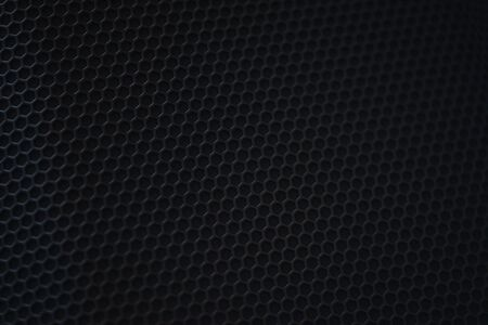 Protective decorative metal grill with honeycombs on modern acoustic systems. Music speakers close-up. Abstract background closeup, soft focus and beautiful bokeh.