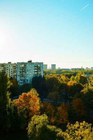 Dense urban development, buildings, city at dawn. Sun flare. Smog and fog over the city. Modern construction of residential buildings. Wires and power supply. Stock fotó