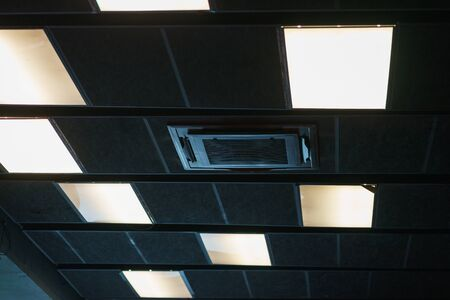 Black design and details of the modern device ceilings in the room. Devices for ventilation air conditioning, ceiling speakers and lighting devices. Details of the modern interior. 版權商用圖片