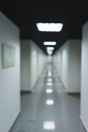 Blurred Interior internal corridor of modern office, industrial premises, laboratories or institutions. Corridor with light walls, black ceiling and shiny floor. Soft focus.