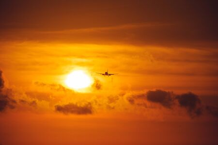 Silhouette of a passenger airliner in the sky during sunset. Airplane in the sky. Take-off and landing, transport and commercial passenger transportation concept. Travel and flights. Фото со стока