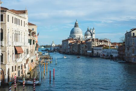 View of Canal Grande, boats and ships on the water with passengers. Cruise, excursions and sightseeing. View of the Basilica di Santa Maria della Salute. Warm autumn day on a trip to Europe. 写真素材