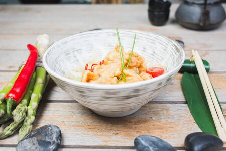 Traditional seafood noodles decorated with pepper and asparagus. Udon, wok, shrimp in batter in a bowl on a wooden table in a restaurant. Oriental, asian serve and decor with palm leaves and bamboo. Фото со стока