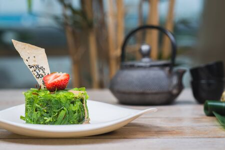 Traditional oriental seaweed salad with peanut sauce on a wooden table in a restaurant. Decor and decoration of palm leaves, Asian dishes. Stock fotó