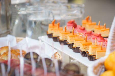 Traditionelles Tiramisu-Dessert in einem Glasbecher auf dem Tisch. Süße kleine Dessertkuchen in verschiedenen Farben auf einem Teller, der für die Gäste der Veranstaltung zubereitet wird.