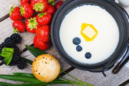 Traditional breakfast. Milk porridge with butter and berries on a wooden table. Classic rustic breakfast, porridge with milk. Healthy tasty food and bright creative serving in the restaurant.