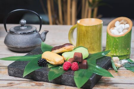 Sweet dessert, eclairs, raspberries and chocolate candies on a wooden table with decor in oriental, asian style. Palm leaves and stone board. Creative presentation and decoration.