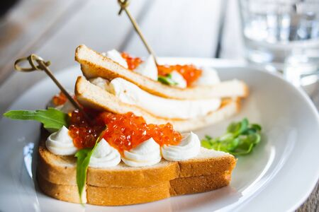 Classic breakfast, hot sandwich with red salmon caviar and mozzarella on a plate on a wooden table. Hand-made, rustic breakfast, toast with caviar, cheese and greens. Soft focus. Foto de archivo - 137789905