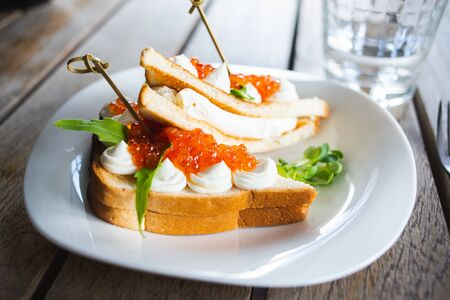 Classic breakfast, hot sandwich with red salmon caviar and mozzarella on a plate on a wooden table. Hand-made, rustic breakfast, toast with caviar, cheese and greens. Soft focus. Foto de archivo - 137790527