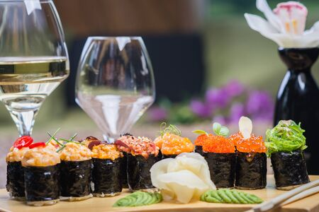 Set of several different rolls on a wooden stand on a table in a Japanese restaurant. Japanese traditional sushi and rolls. Sea products. Beautiful table setting with flowers and wine in glasses.