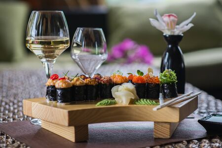 Set of several different rolls on a wooden stand on a table in a Japanese restaurant. Japanese traditional sushi and rolls. Sea products. Beautiful table setting with flowers and wine in glasses. Standard-Bild