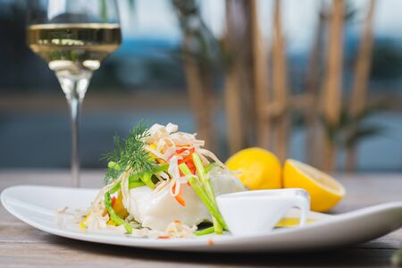 White fish seabass fillet with vegetables and white wine on a wooden table in a restaurant with decor. Tasty and healthy food. A cozy evening in a restaurant during a date. Beautiful table setting.
