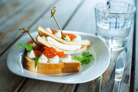 Classic breakfast, hot sandwich with red salmon caviar and mozzarella on a plate on a wooden table. Hand-made, rustic breakfast, toast with caviar, cheese and greens. Soft focus.