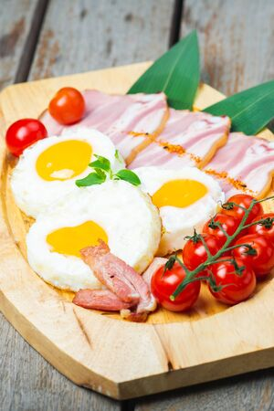 Tasty fried eggs with vegetables on a wooden plate. Creative serving of dishes in the restaurant. Classic breakfast with eggs and tomatoes.