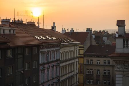 View of the roofs of historic buildings with red tiles during a bright sunset in Prague, Czech Republic. Silhouettes of buildings and roofs in the city. Travel to Europe. Soft focus and bokeh.