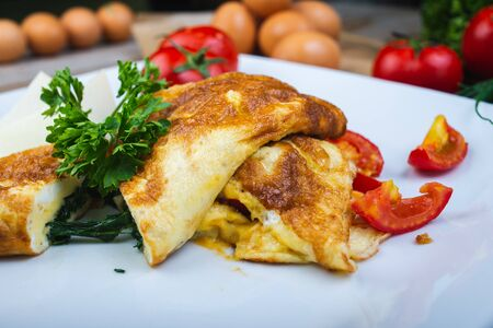 Traditional omelet with vegetables, spinach, tomatoes and herbs on a wooden table in a restaurant. Classic european breakfast. Fried eggs with milk and cheese. Soft focus.