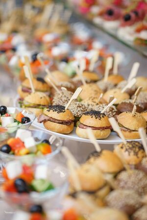 Mini burgers with meat and fish on the table prepared for the guests of the event. Catering and guest meals during the event. Quick mini snacks in a special beautiful dish.