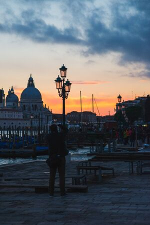View of the Grand Canal and Basilica di Santa Maria della Salute in Venice during sunset. Traditional gondolas and gondolier silhouette. World famous tourist attractions and interesting places. Standard-Bild