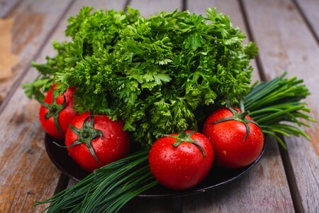 Fresh bright vegetables and herbs on a wooden table. Harvest on a rustic table. Ingredients for salads and vegetable dishes. Vegetarian. 写真素材